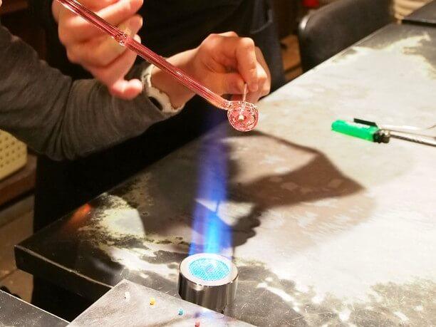 溶けてきたガラスの先端を棒に巻き付ける作業