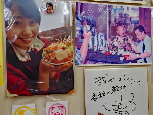 壁に貼られた写真やサイン色紙