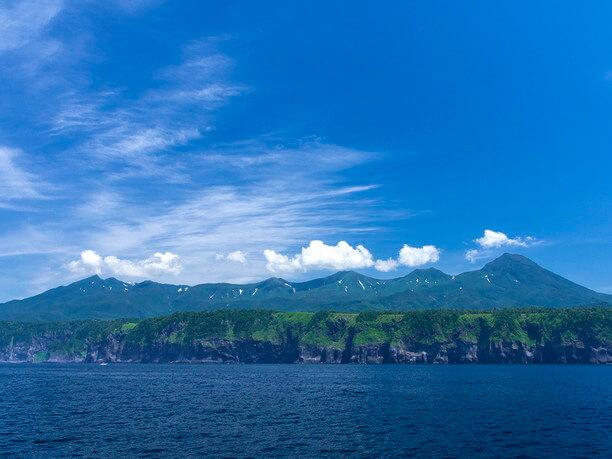 断崖の海岸の上にそびえる知床の山々