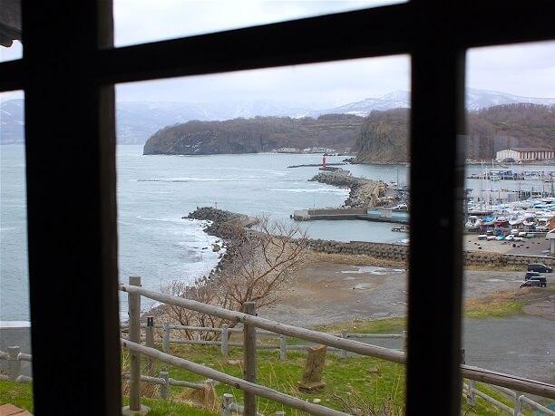 窓から見える青い海と港