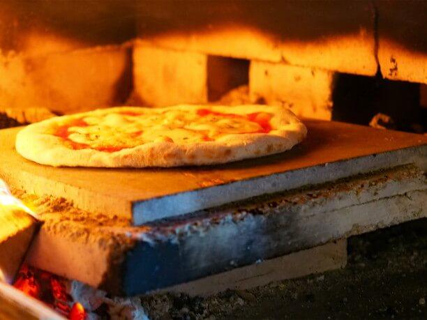 溶岩を使ったプレートで焼かれるピザ生地