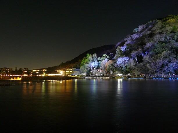 桂川の水面に映り込むライトアップされた背後の嵐山や街の灯り