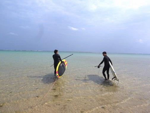 ボードをもって海へ向かう二人