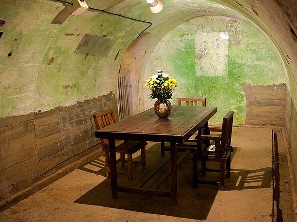 木製のテーブルと椅子が置かれた司令官室