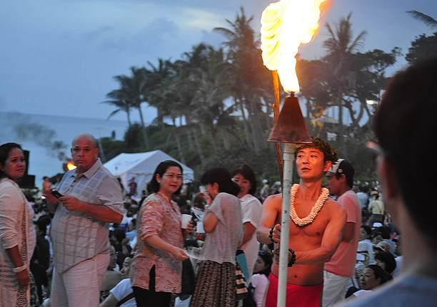 法螺貝の音とともに男が会場内にたいまつを灯す