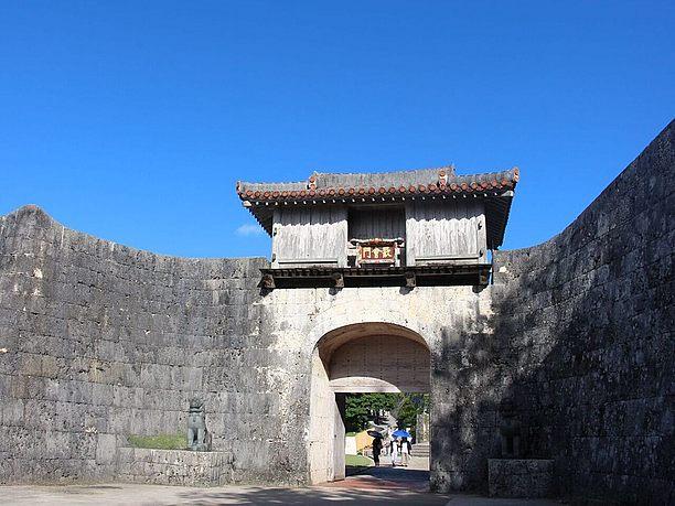 石の城壁とその上に木造のやぐらが乗った門