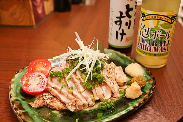 オリジナルポン酢をつけて食べる鶏のタタキ