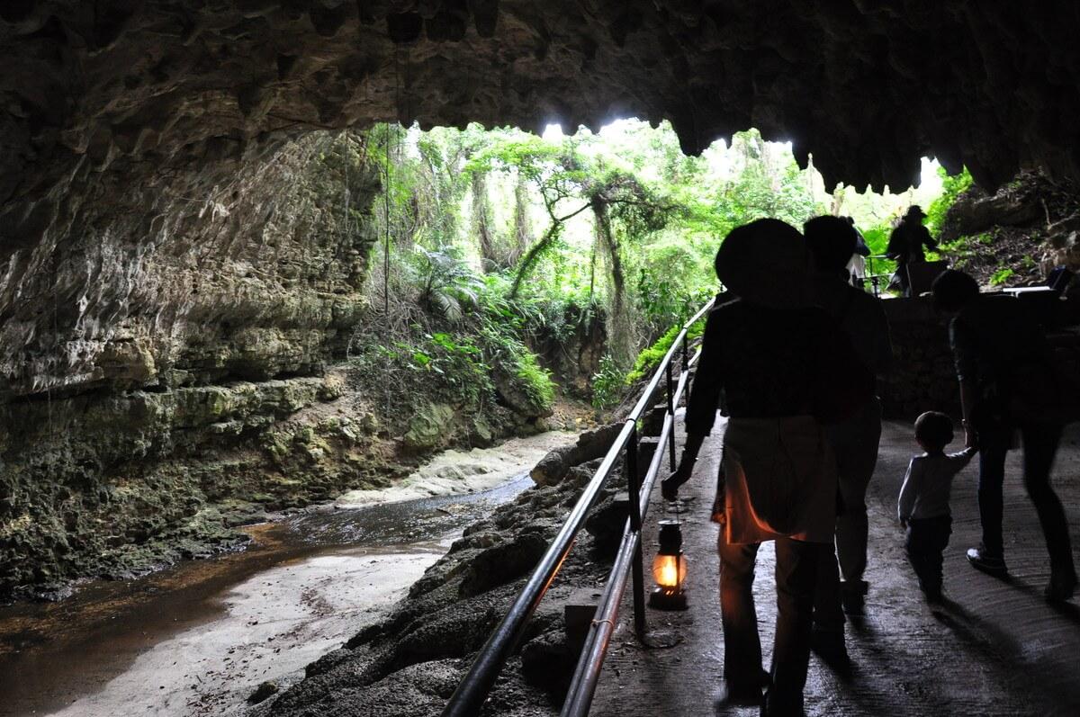 天井の低い洞窟へランプを持って奥へと進んでいくスポットも