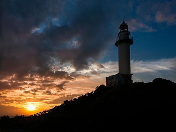 灯台も雲も夕日に染まる