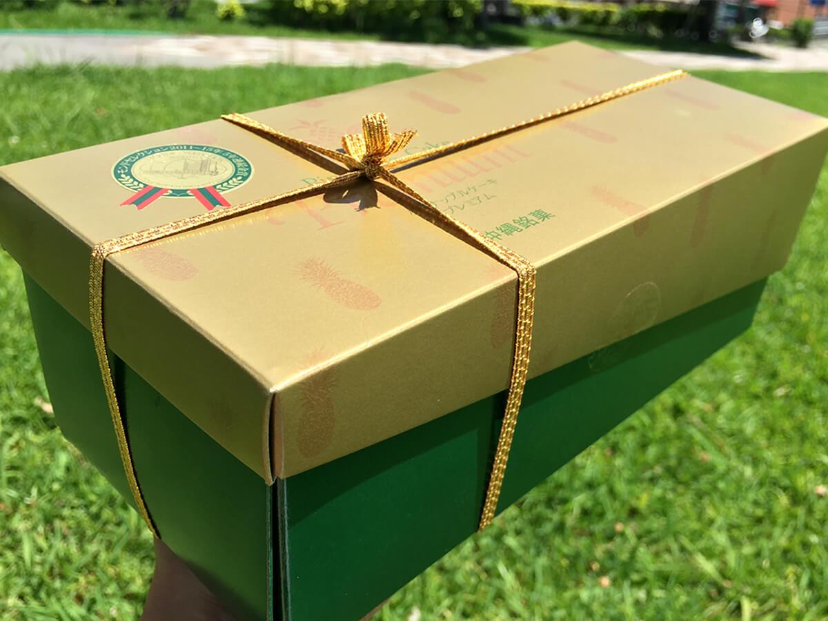 高級感のある深緑の箱が金色のリボンで飾られています