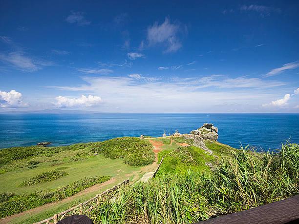 広がる青い海の向こうにかすかに見えるのは西表島