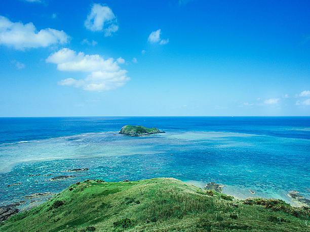 灯台の立つ小さな丘から一面の海を見渡す