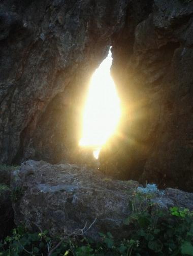 岩の穴の間から見られる日の出