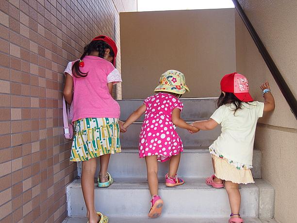手をつないで階段を上る子供たち