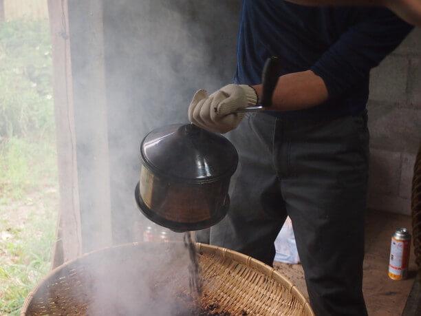 ざるの中へ移される熱々のコーヒー豆