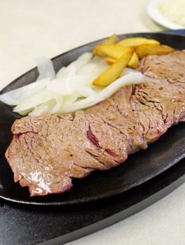 熱々の鉄板皿にのったステーキ