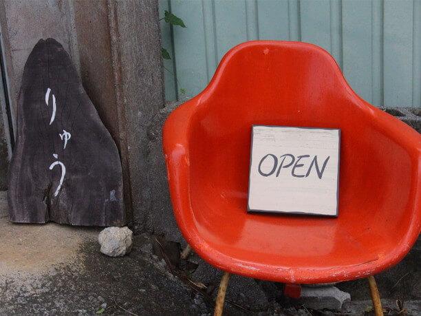 赤い椅子の上にOPENと書かれたプレート