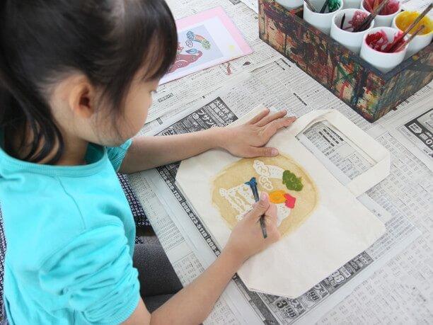 絵の具でモチーフを染める子供