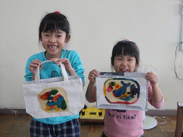 体験終了段階での作品を持って笑顔の子どもたち
