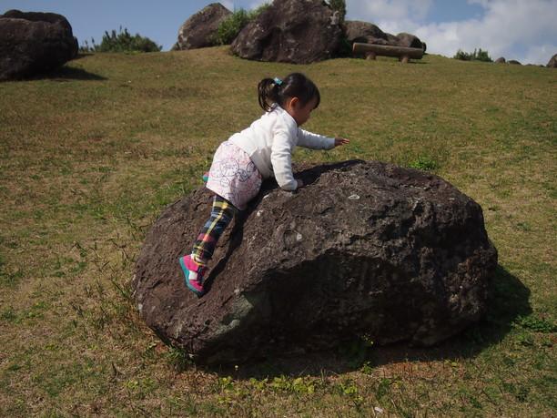 大きな石の上に上る子供