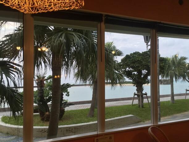 窓越しに見える海と遊歩道