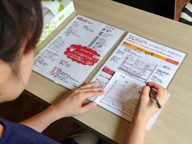 注文用紙にカレーと辛さを記入する様子
